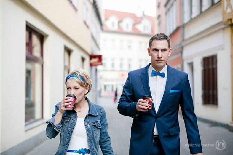Braut und Bräutigam trinken einen Coffee To Go vor der Trauung in Erfurt, Braut in Jeansjacke, Chucks und einem Kleid von Noni. Fotografiert in Erfurt von Melanie Dressel