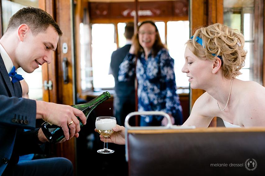 Brautpaar schenkt Sekt ein während Stadtrundfahrt in Erfurt, fotografiert von Melanie Dressel
