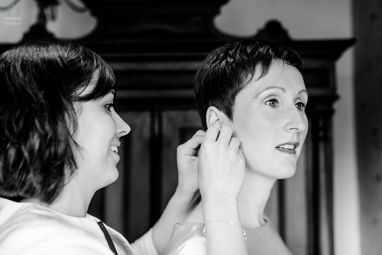 Schwester der Braut hilft beim Schmuck anlegen, fotografiert von Melanie Dressel