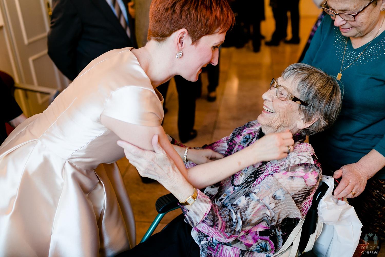 Braut umarmt Frau im Rollstuhl im Standesamt Gera