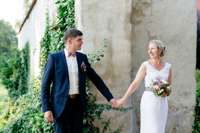 Brautpaar hält Händchen am Eingang zum Schloß Schweinsburg