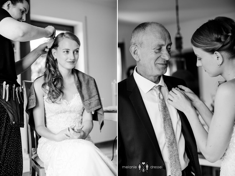 Braut wird firsiert und heftet Vater einen Blumenstrauß ans Revers