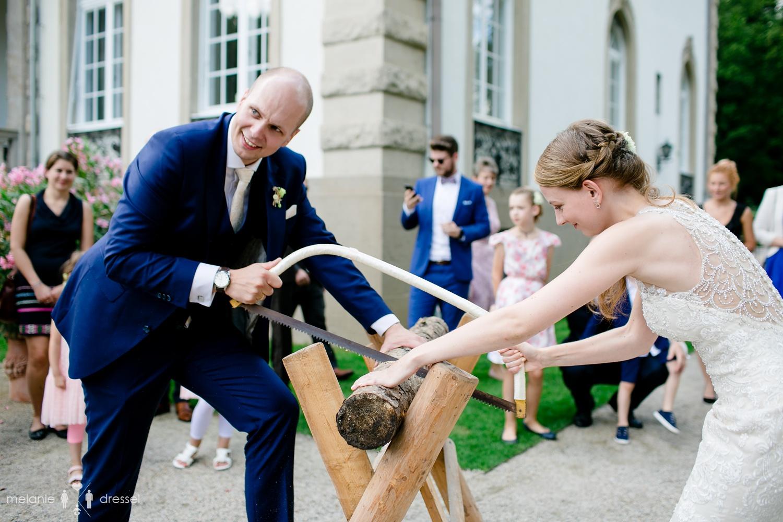 Brautpaar sägt Baumstamm vor der Villa Altenburg