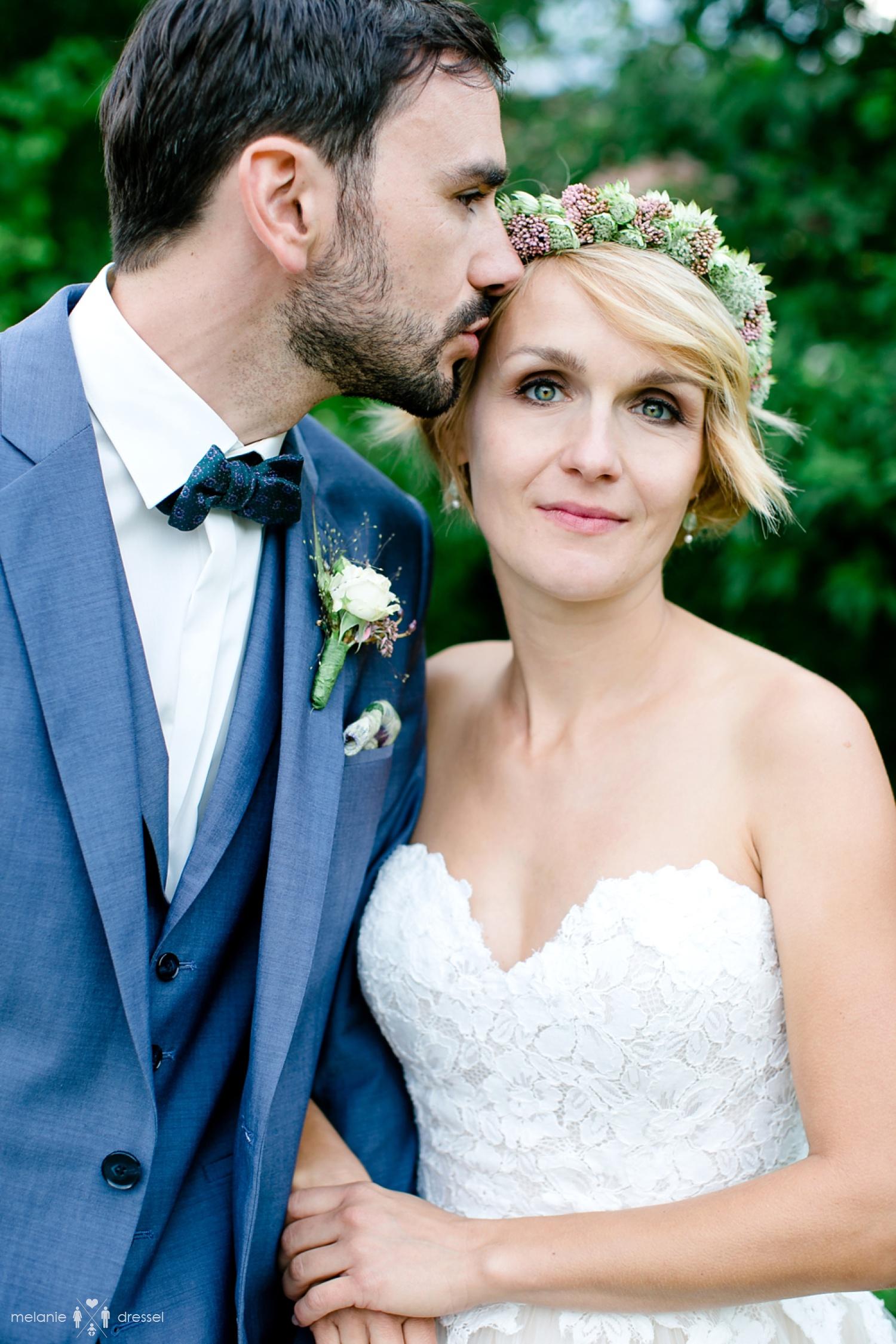 Bräutigam küsst Braut auf die Schläfe während der Fotosession für die Hochzeitsportraits, fotografiert auf dem Wildberghof Buchet von Hochzeitsfotograf Melanie Dressel