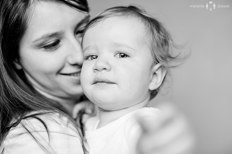 Mama hält Kleinkind mit Träne auf der Wange im Arm