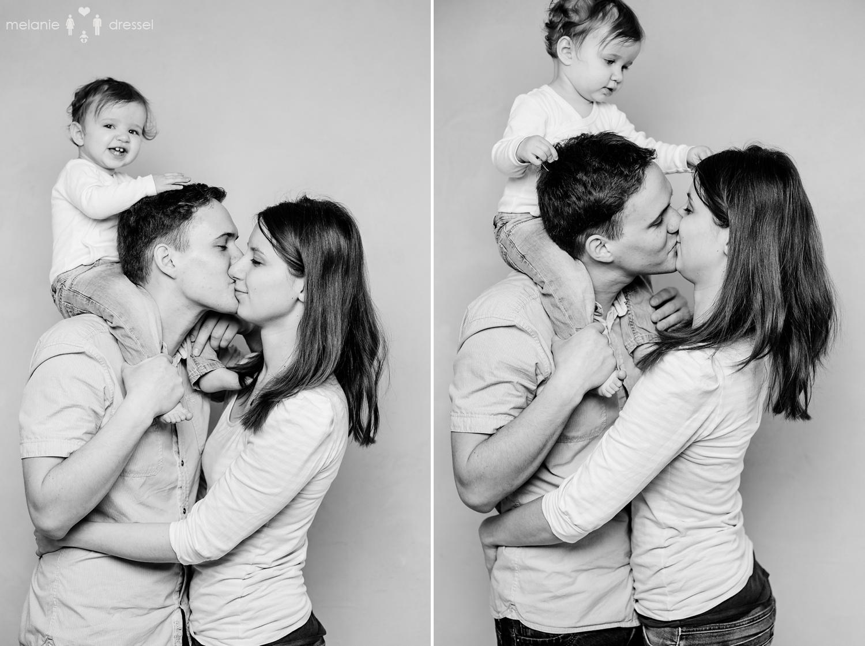 Mama und Papa küssen sich, Papa trägt Kind auf den Schultern