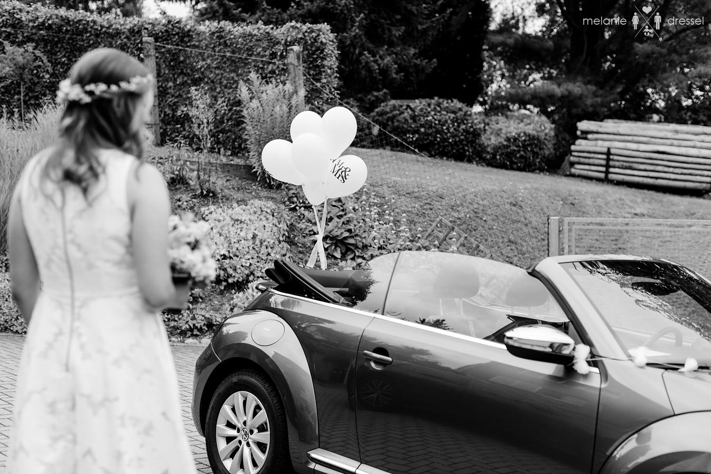 Braut steht vor Brautauto. Fotografiert von Melanie Dressel, Gera.