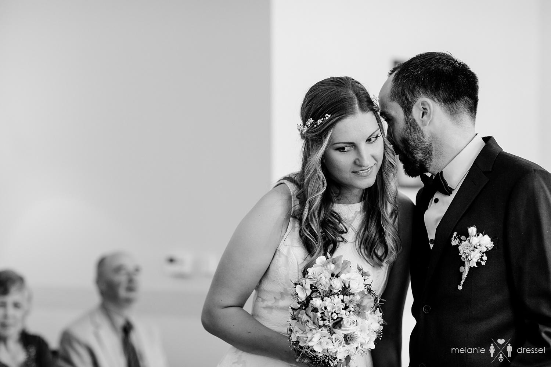 Bräutigam flüsstert Braut etwas ins Ohr. Fotografiert von Hochzeitsfotografin Melanie Dressel, Gera.