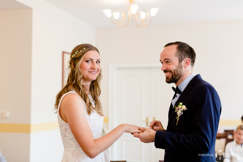 Bräutigam steckt Braut den Ring an den Finger.