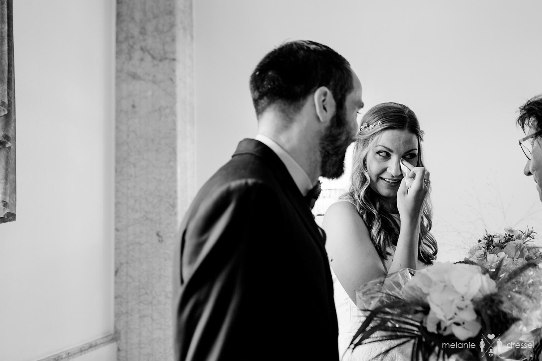 Braut wischt sich Träne aus dem Auge.