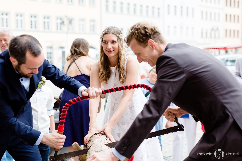 Traditionelles Baumstammsägen vor Standesamt. Fotografiert von Hochzeitsfotografin Melanie Dressel, Gera.