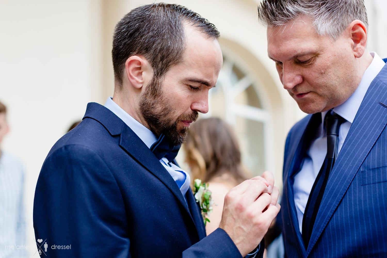 Bräutigam und Schwiegervater betrachten Eheringe. Fotografiert von Hochzeitsfotografin Melanie Dressel, Gera.