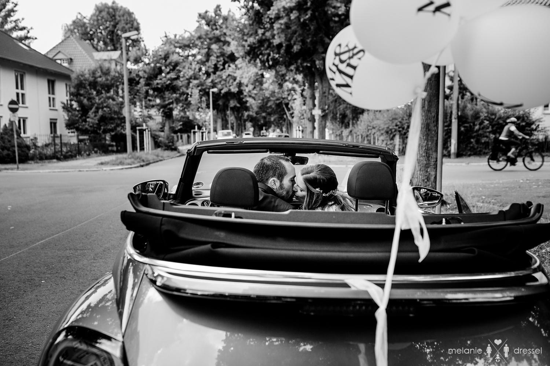 Brautpaar küsst sich in einem VW Beetle. Fotografiert von Hochzeitsfotografin Melanie Dressel, Gera.